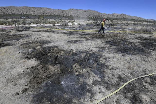 A fire fighter look over the crash site of a two-seater single engine S312 Tucano aircraft north of Santa Barbara